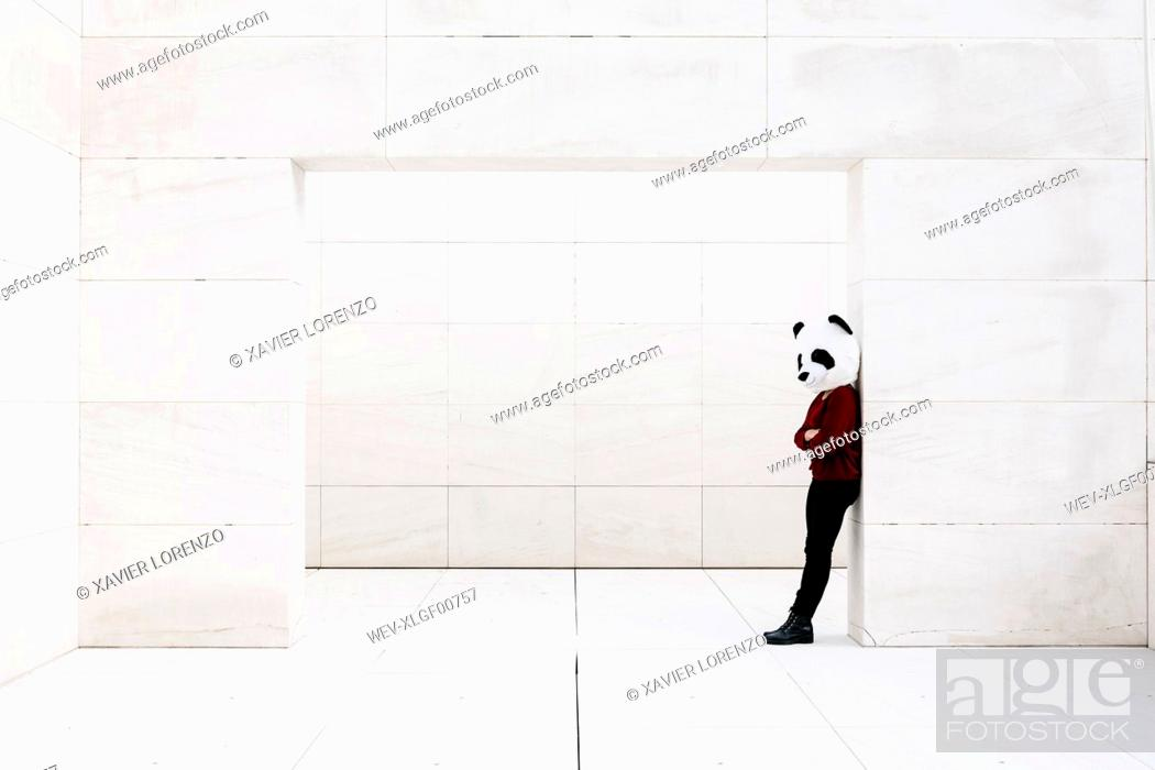 Stock Photo: Depressed woman with arms crossed standing at doorway against wall.