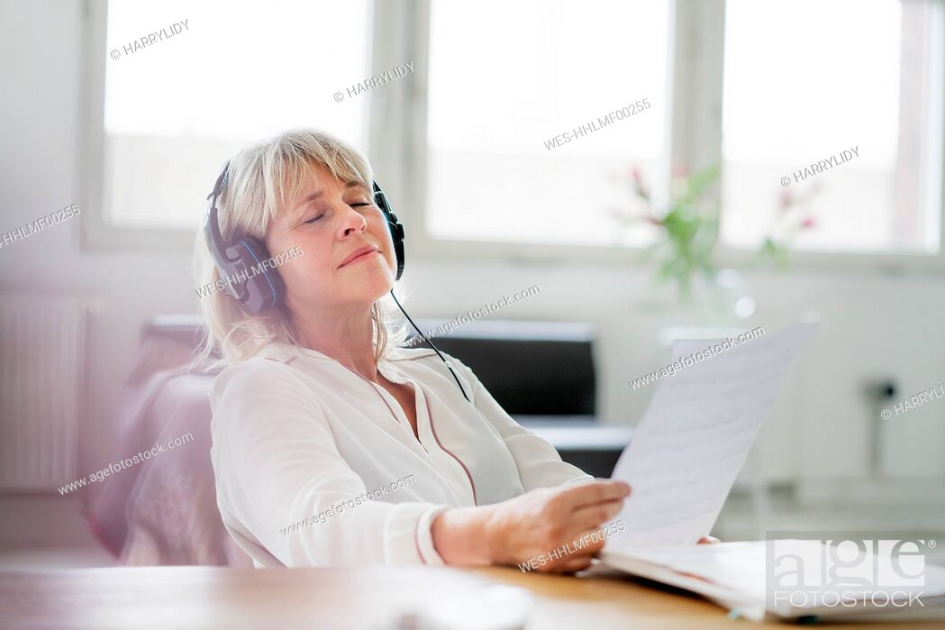 Stock Photo: Relaxed mature businesswoman wearing headphones at desk.