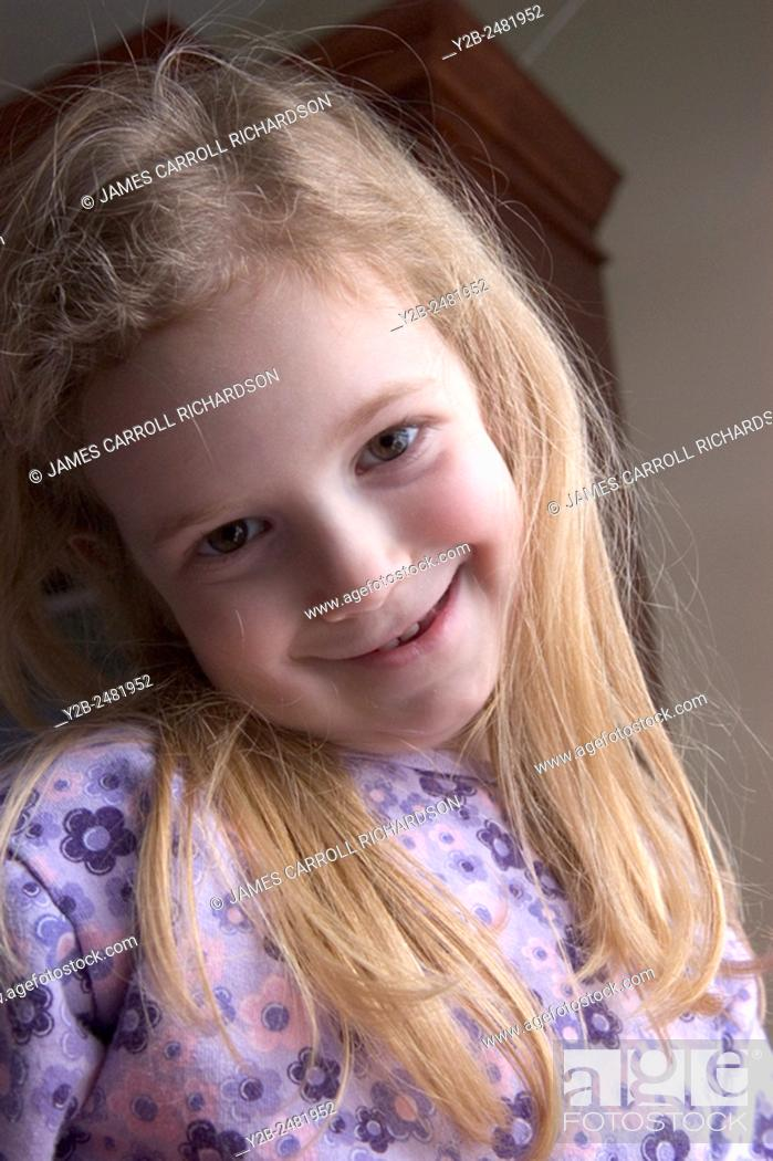 Stock Photo: Young girl with long blond hair smiles shyly.