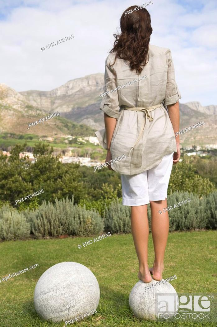 Stock Photo: Woman standing on a round stone and looking at a view.