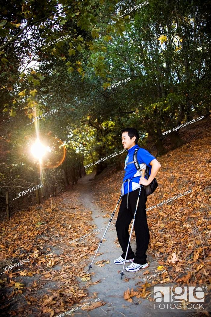 Stock Photo: The early morning sun peaks through the trees as a male Korean hiker takes a break in a tree covered area of the Peak Trail at Mission Peak Regional Preserve in.