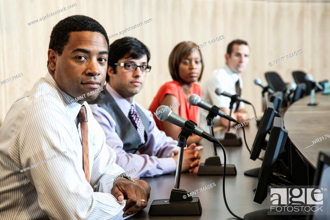 Stock Photo: A group of men and a woman, an ethnically diverse panel of politicians sitting with microphones in a political meeting.