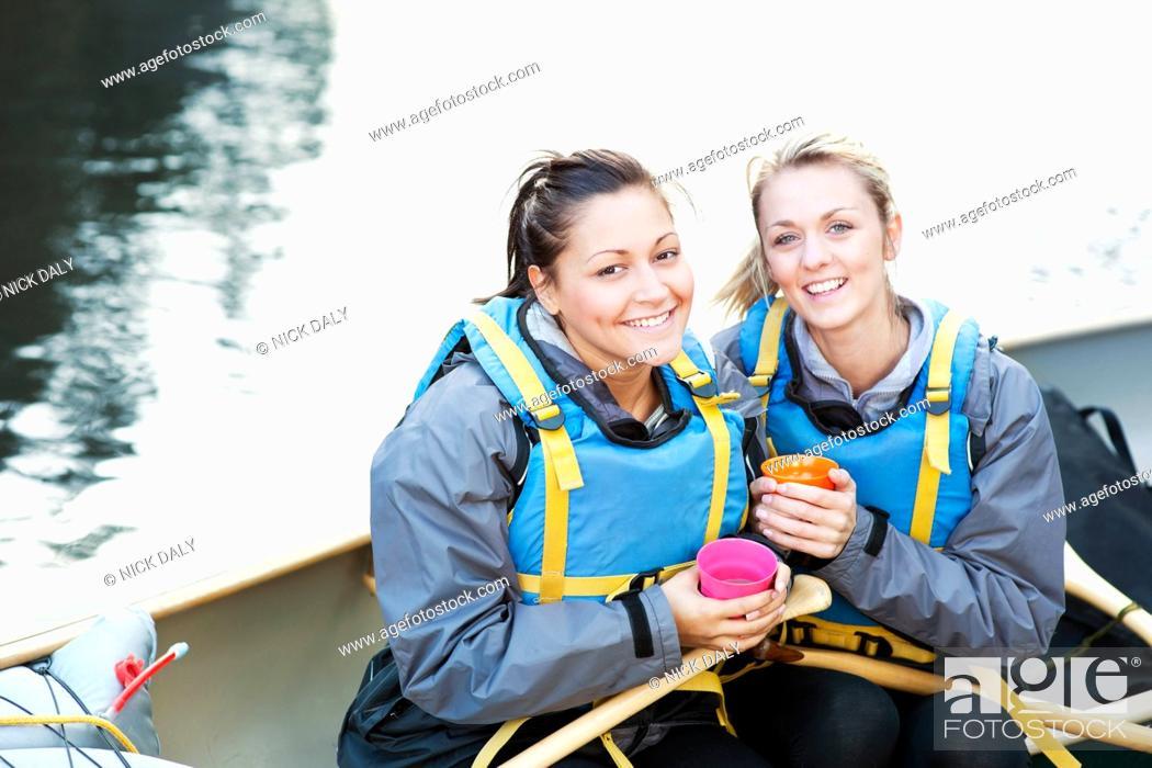 Stock Photo: Women having coffee in canoe.