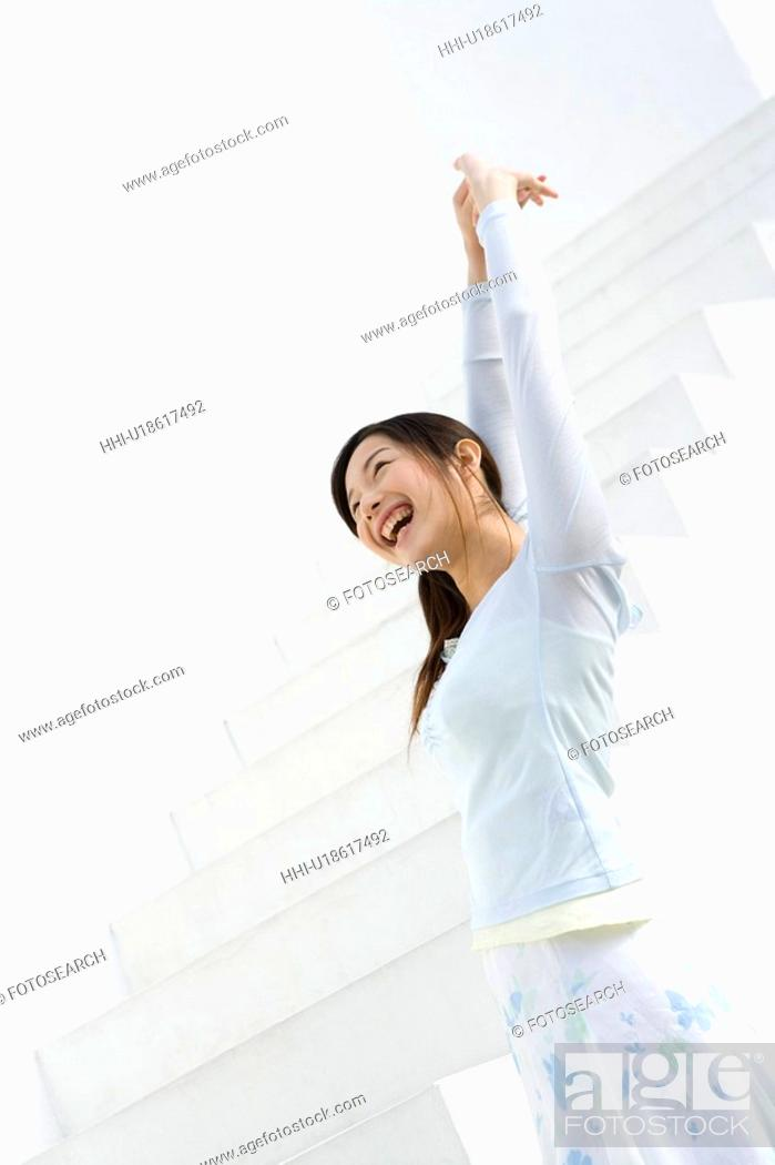 Stock Photo: A woman smiling and stretching arms at the stairs, side view, low angle view.