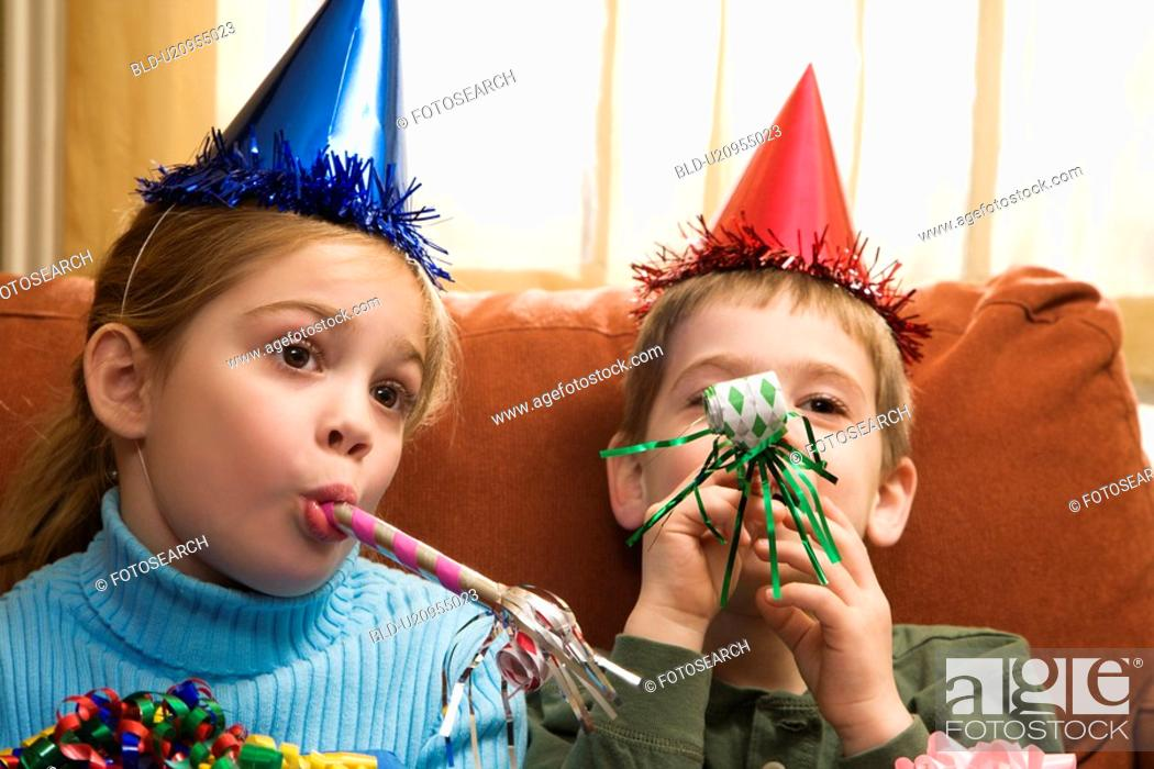 Stock Photo: Caucasian children looking bored wearing party hats and blowing noisemakers.