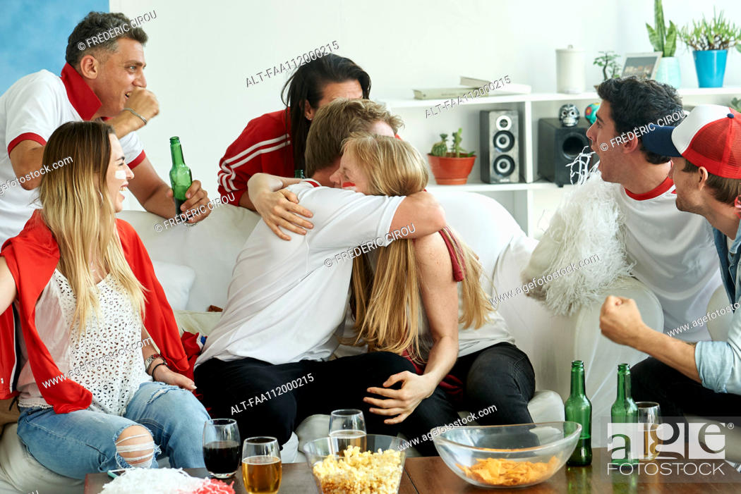 Stock Photo: English soccer fans watching match together at home.