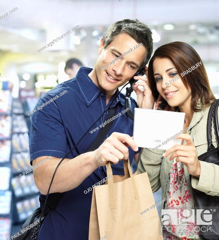 Stock Photo: Couple sharing headphones and looking at CD.