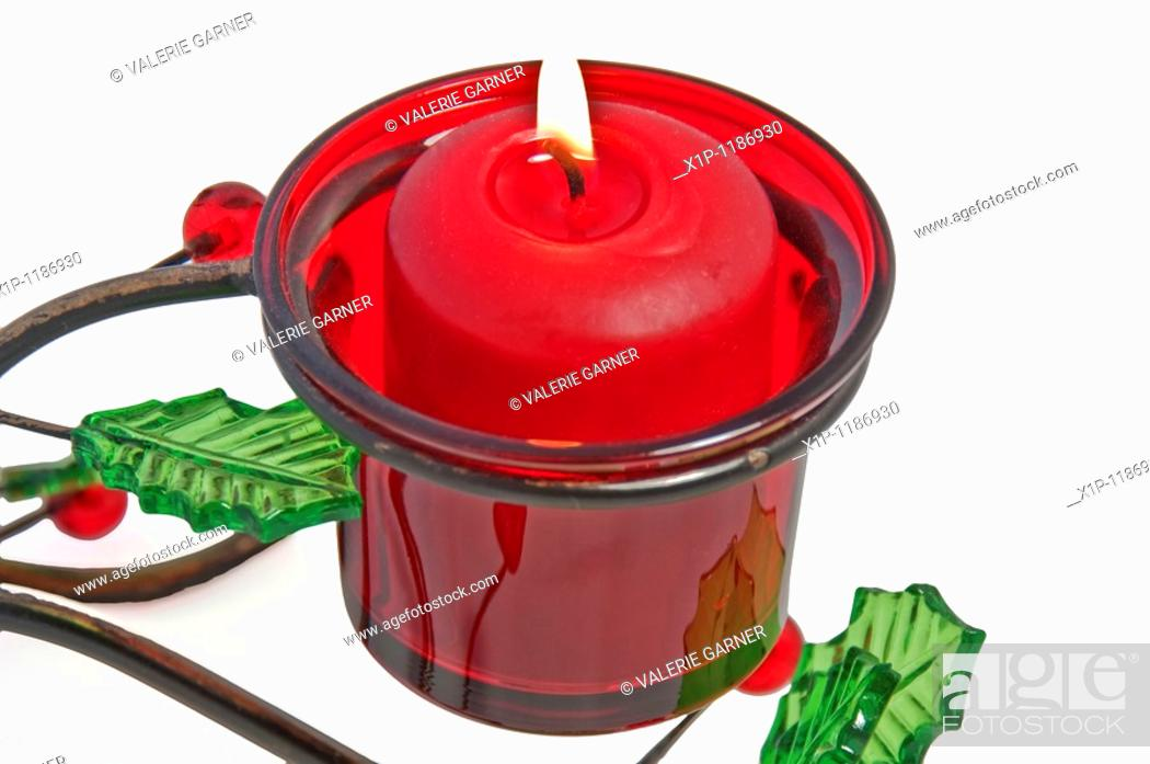 Stock Photo: This red votive candle is lit and burning in a Christmas holder that is metal with glass holly leaves and berries, isolated on a white background.