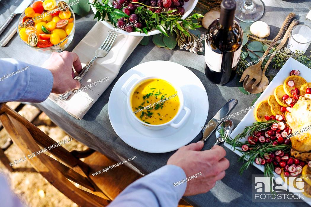 Stock Photo: Caucasian man setting platter of soup on outdoor table.