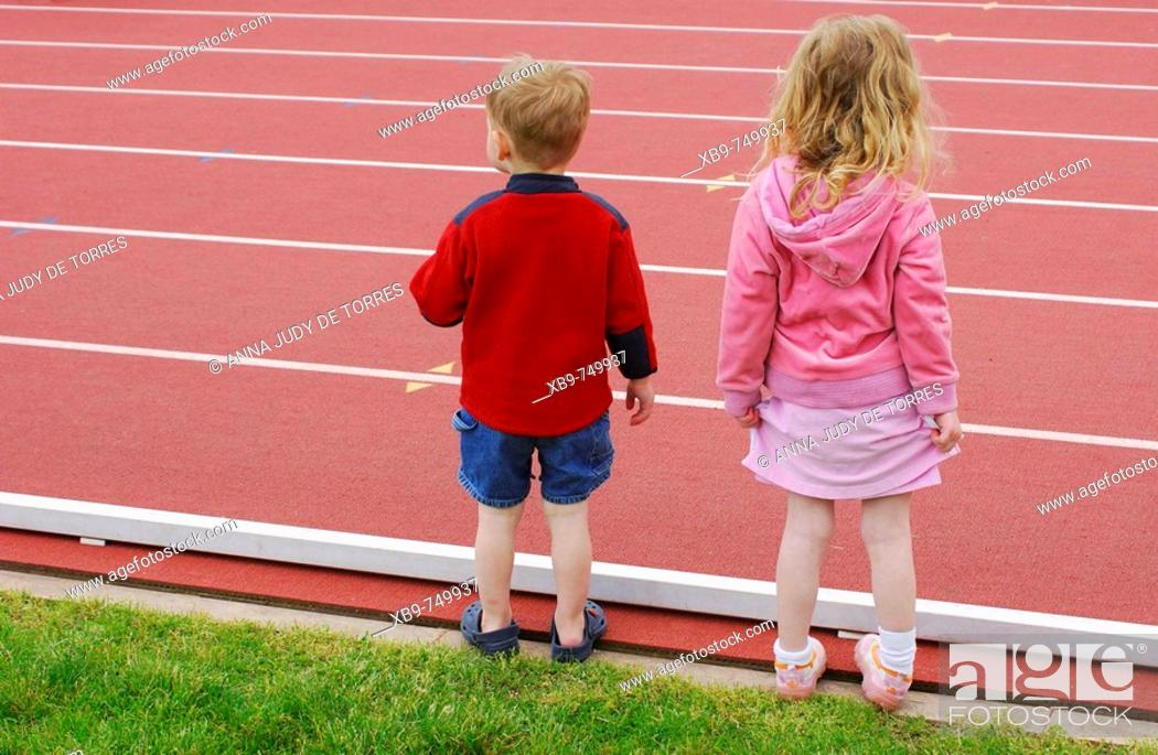 Stock Photo: A little boy and girl stand beside a track.