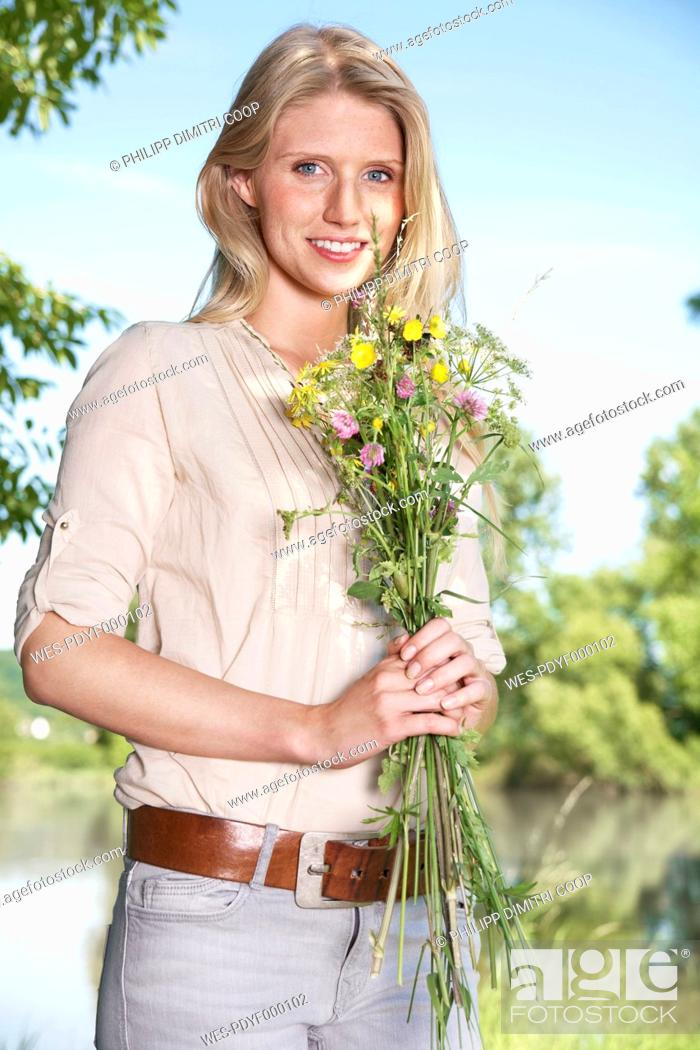 Stock Photo: Germany, Cologne, Young woman holding wild flowers, smiling, portrait.