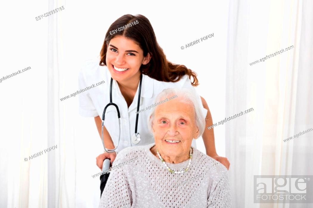 Stock Photo: Portrait Of Happy Female Doctor With Handicapped Senior Patient In Hospital.