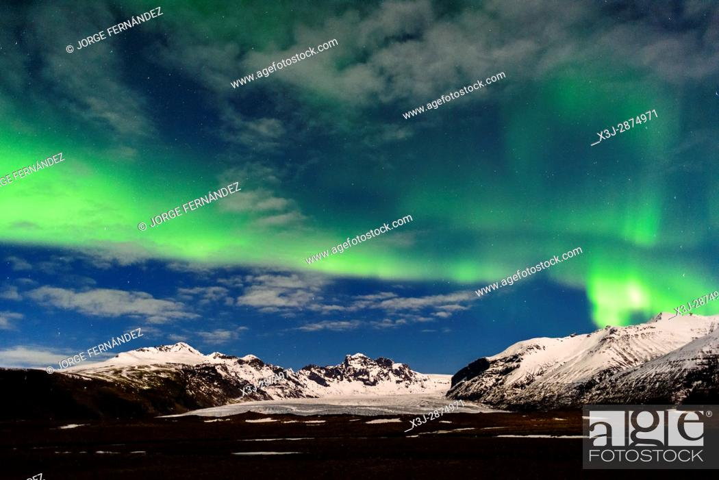Stock Photo: Green auroras over the mountains in the winter skies of Iceland.
