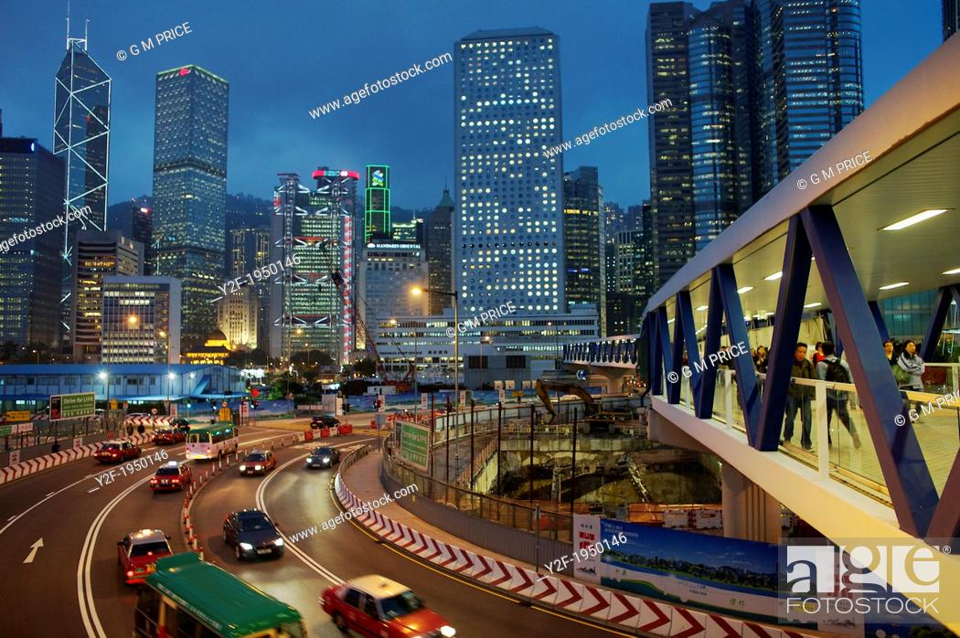 Imagen: people and traffic pass through Central Hong Kong construction zone at dusk.