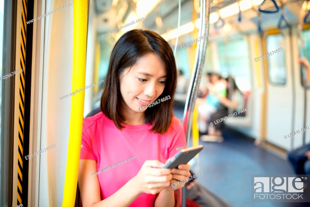 Stock Photo: Woman use of cell phone inside train compartment.