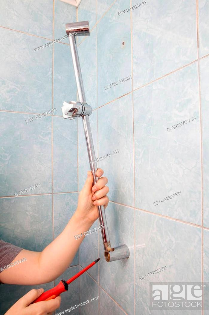 Imagen: Close-up hands uninstalling the broken vertical height adjustable shower bar slider rail holder, using red phillips screwdriver.