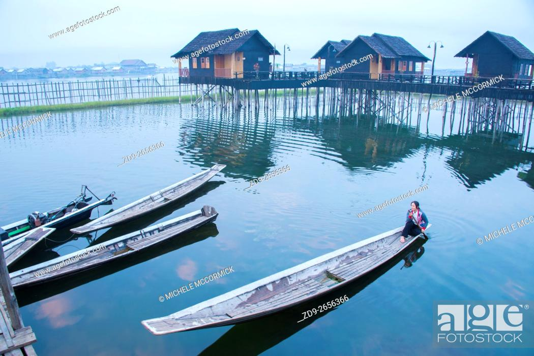 Stock Photo: An early morning boater sets out from Garden Island Cottages at Inle Lake.