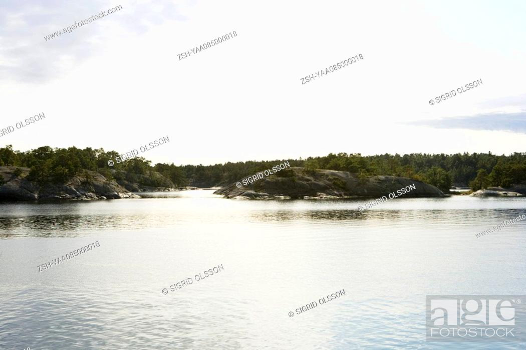 Stock Photo: Lake scene with rocky shore and forest in background.