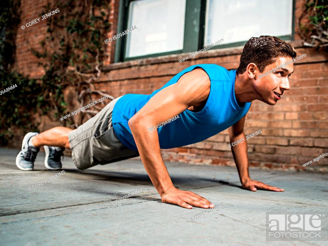 Stock Photo: Young man doing push-up on city street.