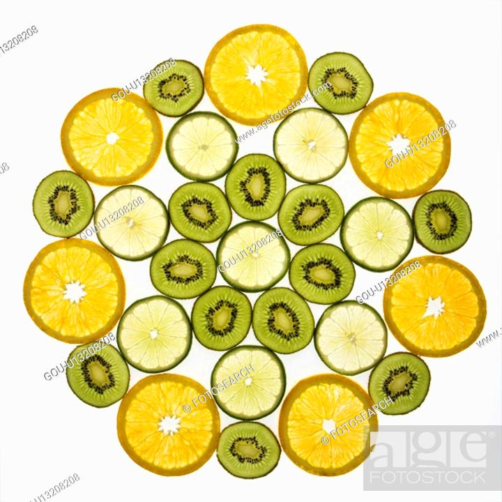 Stock Photo: Assorted fruit slices arranged in pattern on white background.