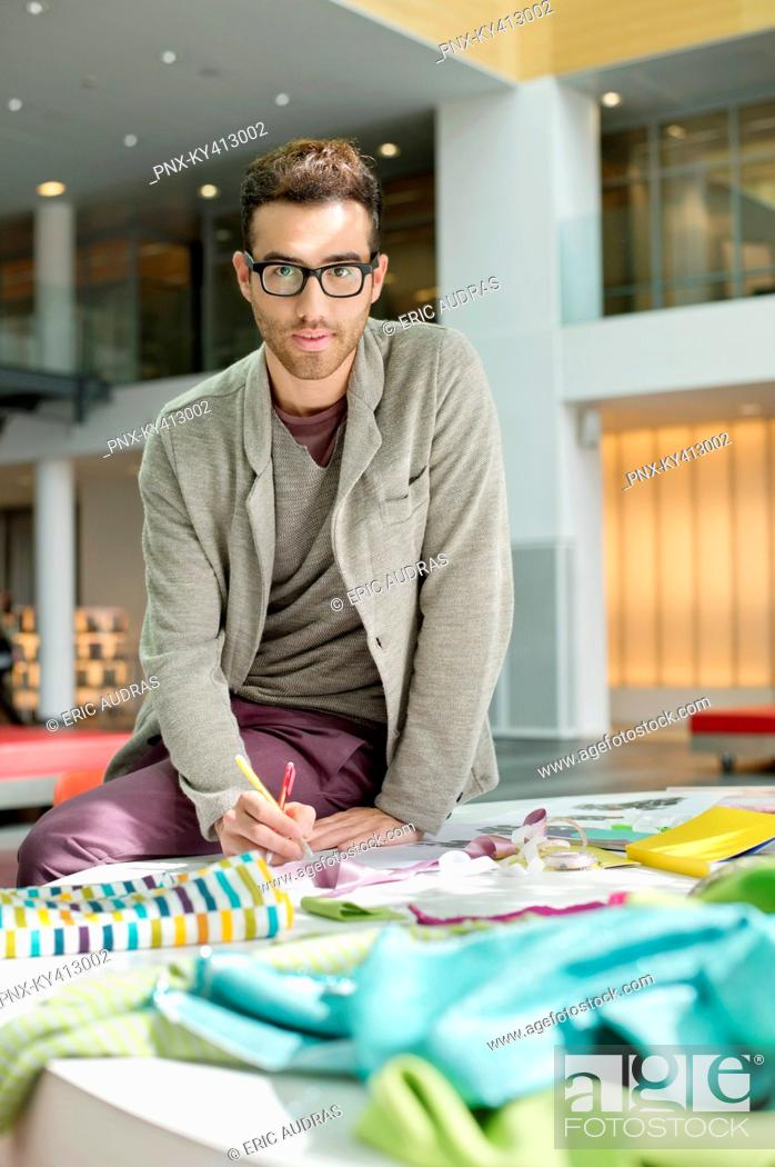 Stock Photo: Male fashion designer working in an office.