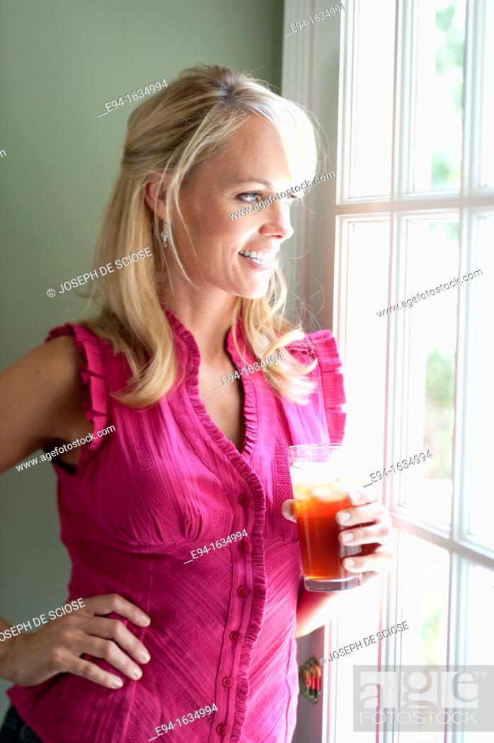 Stock Photo: 35 year old blond woman standing in a kitchen holding a glass of iced tea looking out a window away from the camera.