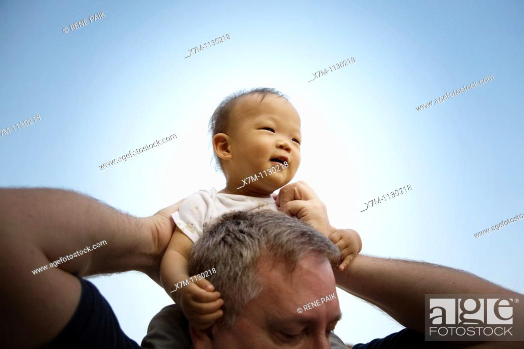 Stock Photo: A Korean baby boy is given a ride on the shoulders of a large Caucasian man.
