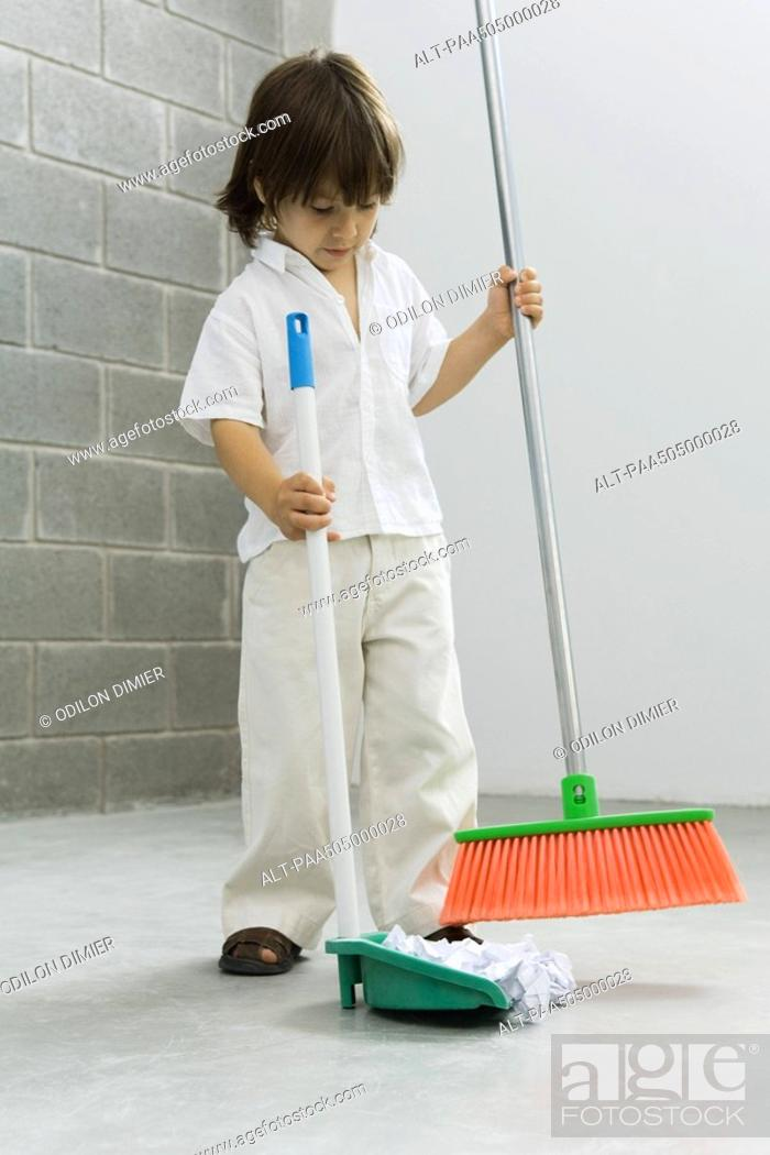 Stock Photo: Little boy sweeping the floor.