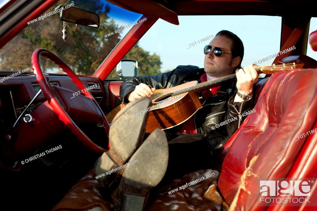 Stock Photo: A rockabilly guy playing an acoustic guitar while sitting in his vintage car.