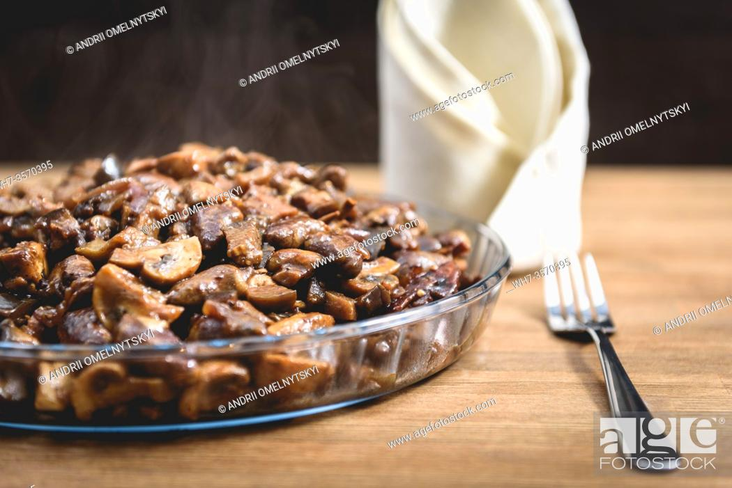 Stock Photo: vegetable stew in a glass dish on the table, next fork and napkin.
