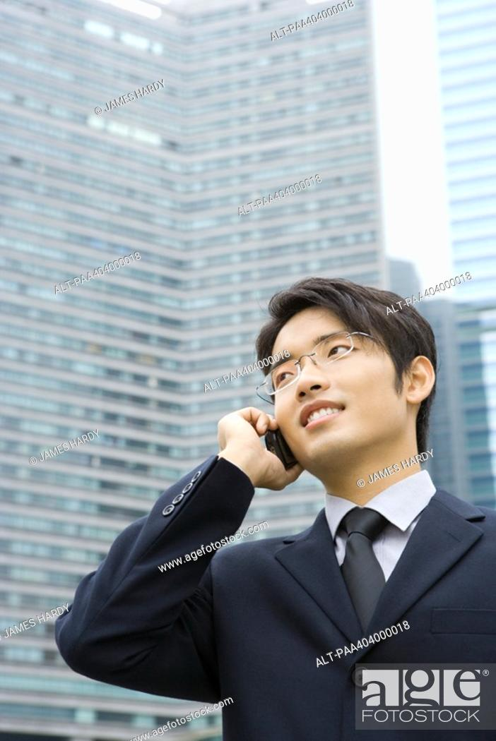 Stock Photo: Young businessman using cell phone, looking away, office building in background.