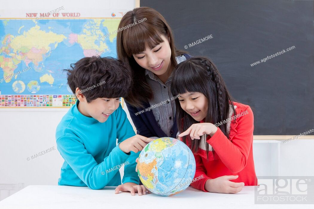 Imagen: Young teacher and students looking at the globe and studying,.