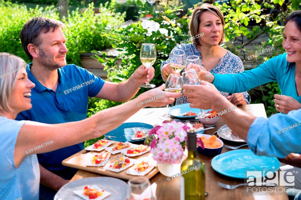 Stock Photo: Group of friends gathered around a table in a garden on a summer evening to share a meal and have a good time together.