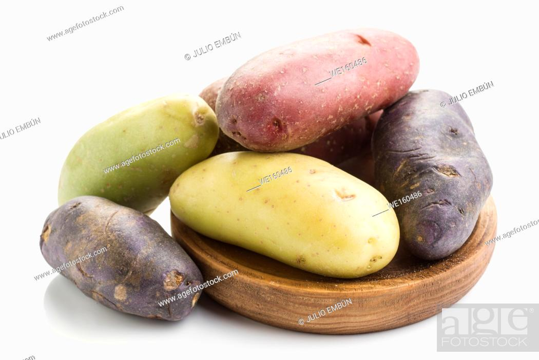 Stock Photo: colorful potatoes on wooden board isolated on white.