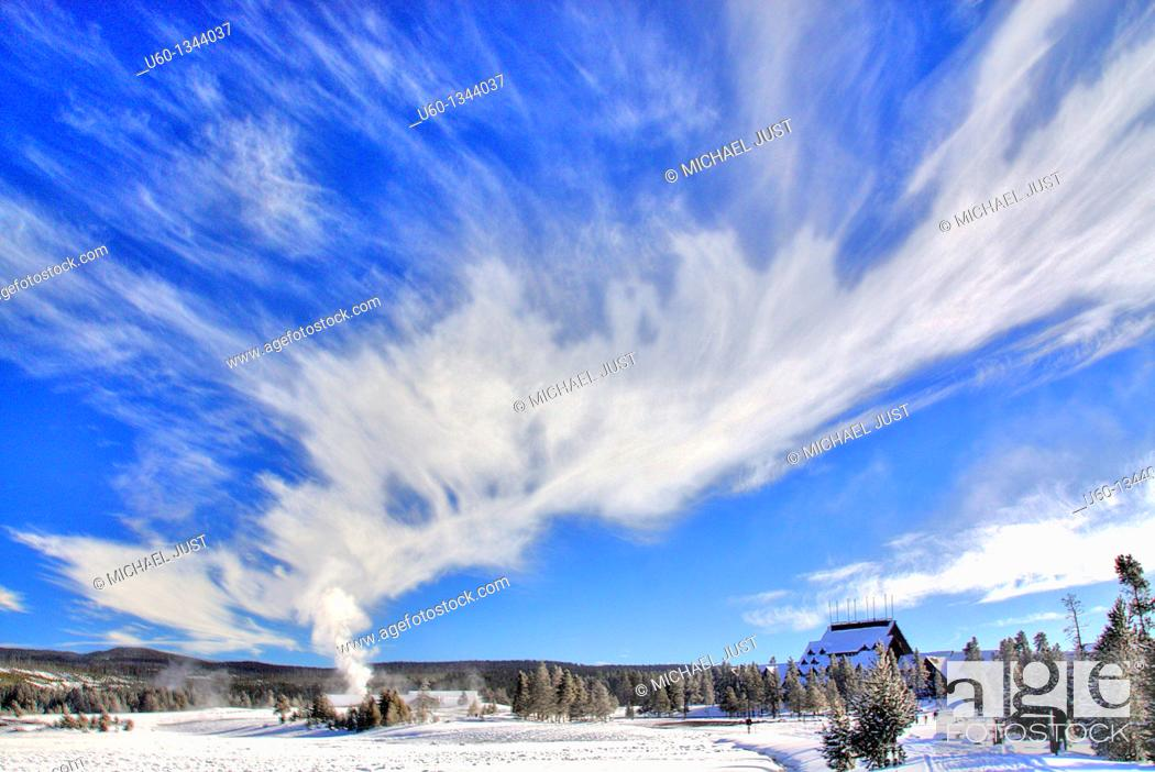 Stock Photo: The sky is filled with steam as Old Faithful Geyser erupts near The Old Faithful Inn during winter at Yellowstone National Park, Wyoming.