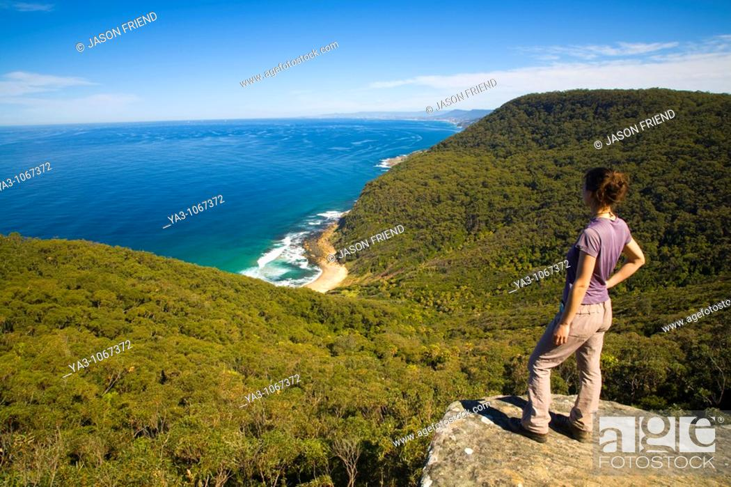 Stock Photo: Australia, New South Wales, Royal National Park  Female hiker walking the coastal path takes a break to look down on Werrong Beach from a rocky lookout above.