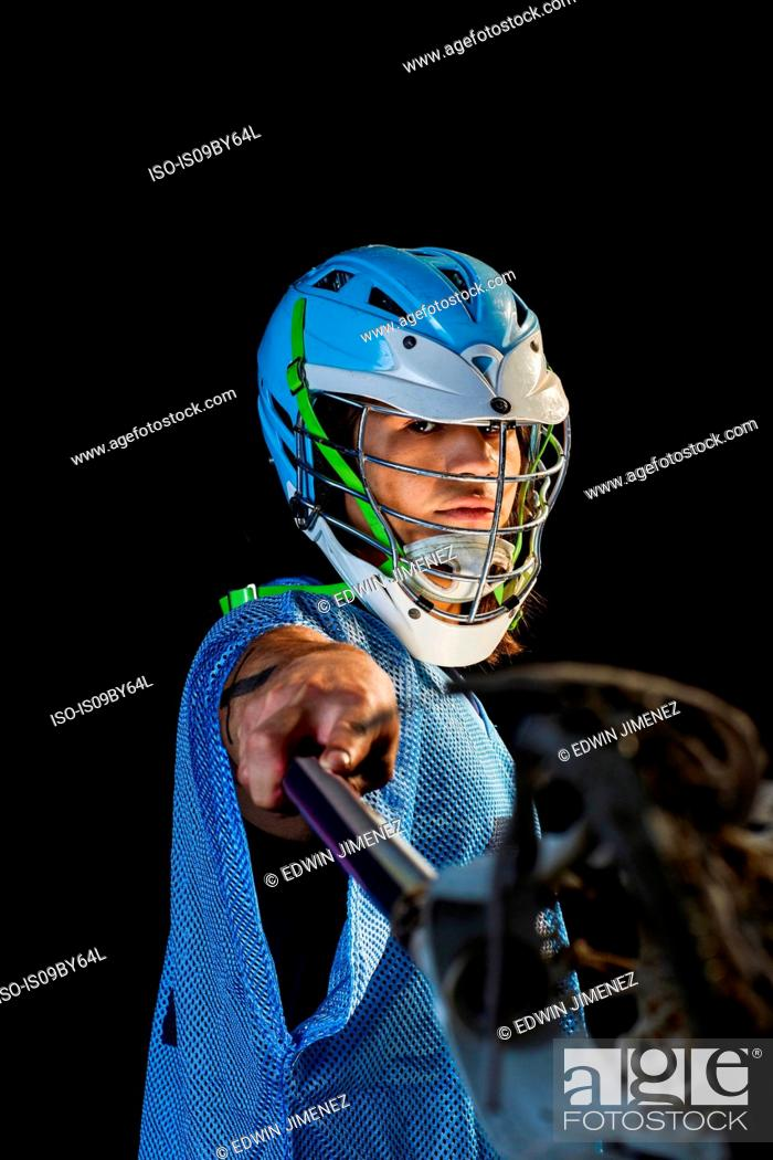 Stock Photo: Young male lacrosse player lunging with lacrosse stick, portrait against black background.