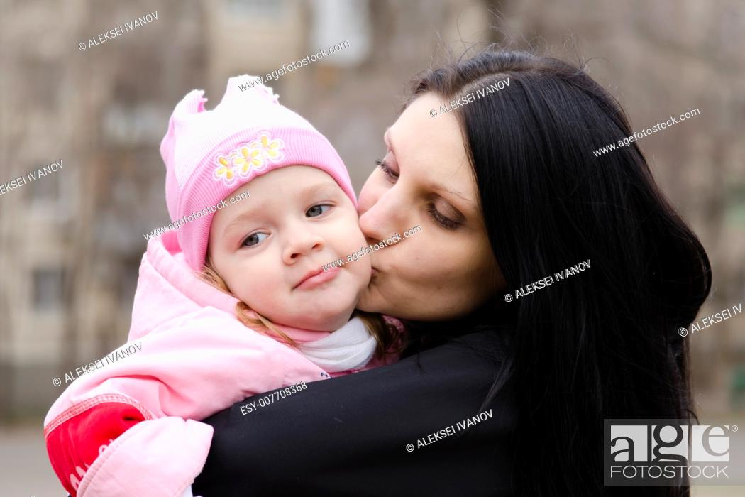 Imagen: Little girl keeps mum on his hands. The girl thoughtfully laid her head on her mother's shoulder. A warm spring day.
