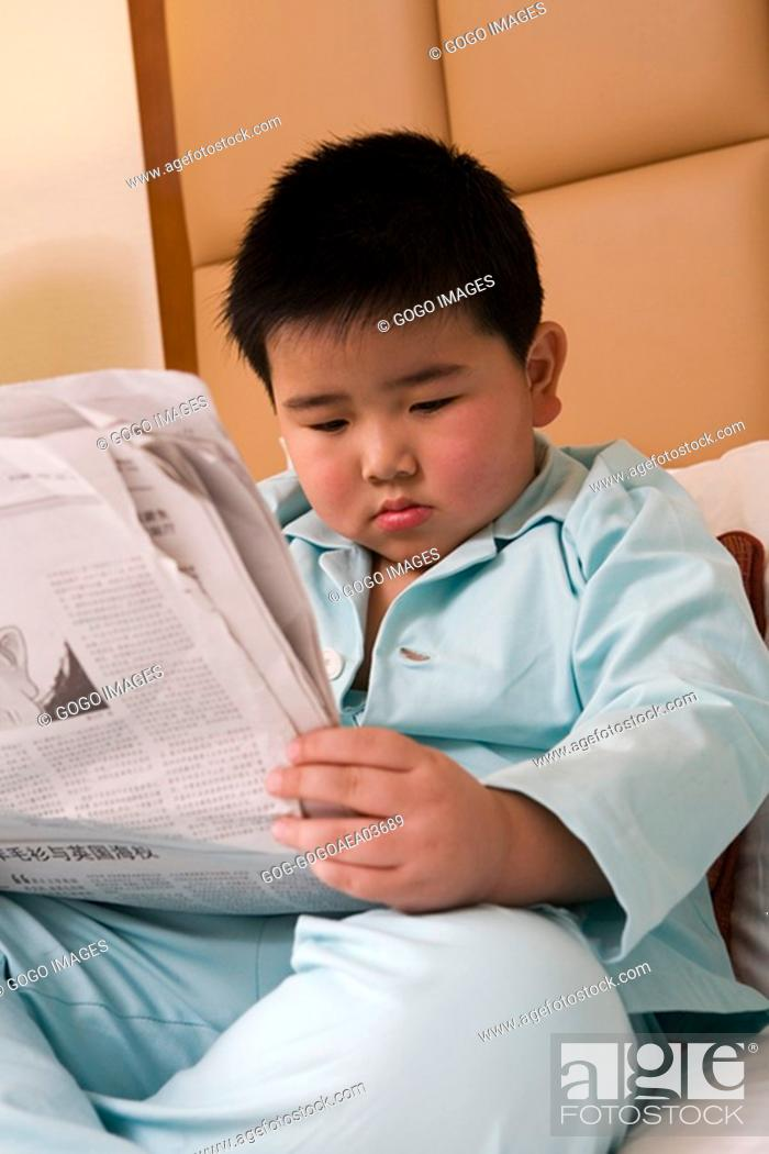 Stock Photo: Young boy reading newspaper in bed.