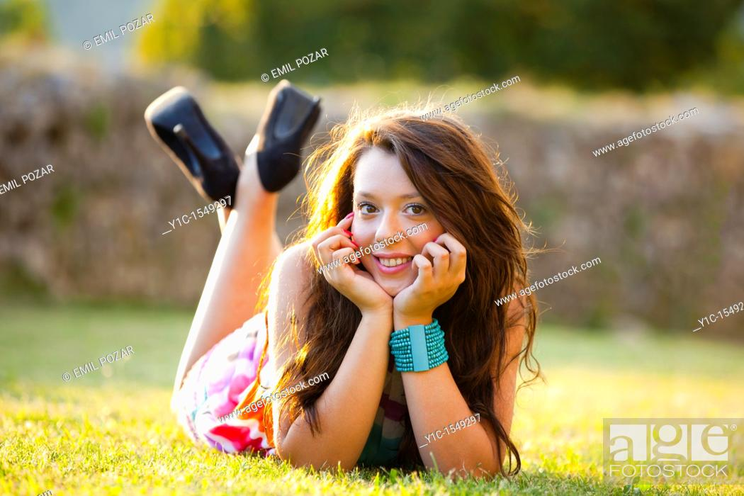 Stock Photo: Lying on a grass and smiling young teen woman.