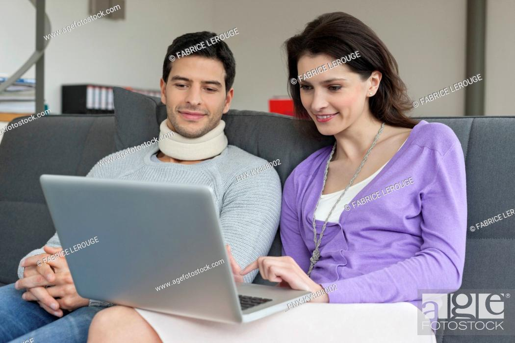 Stock Photo: Woman using a laptop with her husband beside her.