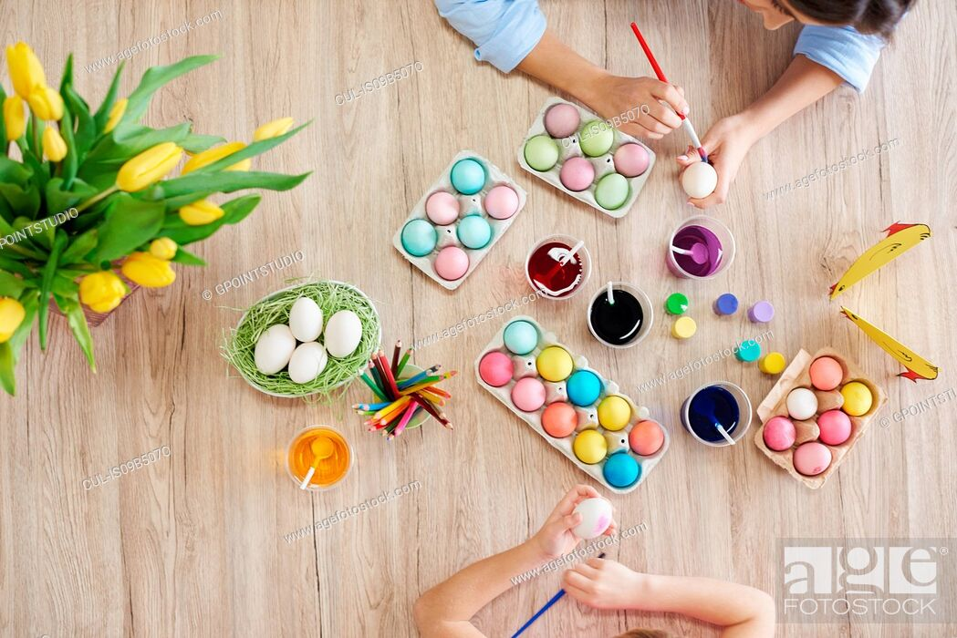 Stock Photo: Overhead view of woman and daughter's hands painting easter eggs at table.