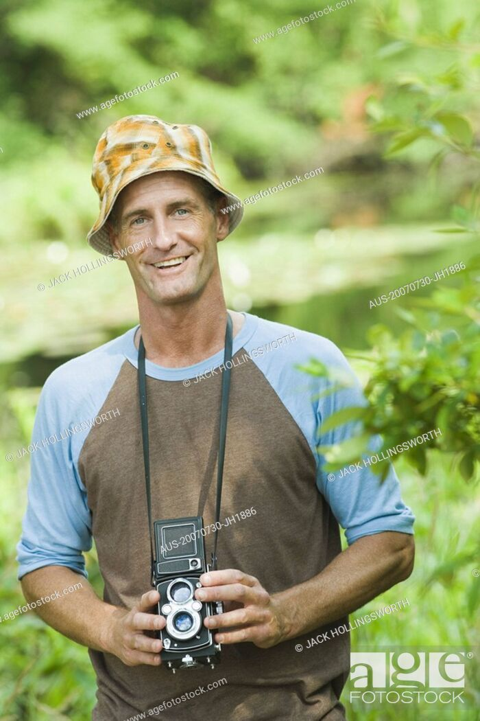 Stock Photo: Portrait of a mature man holding a camera and smiling.