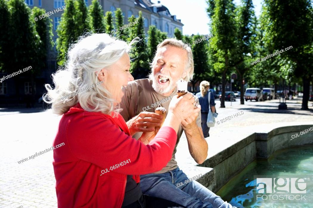Stock Photo: Couple with ice-cream, laughing.
