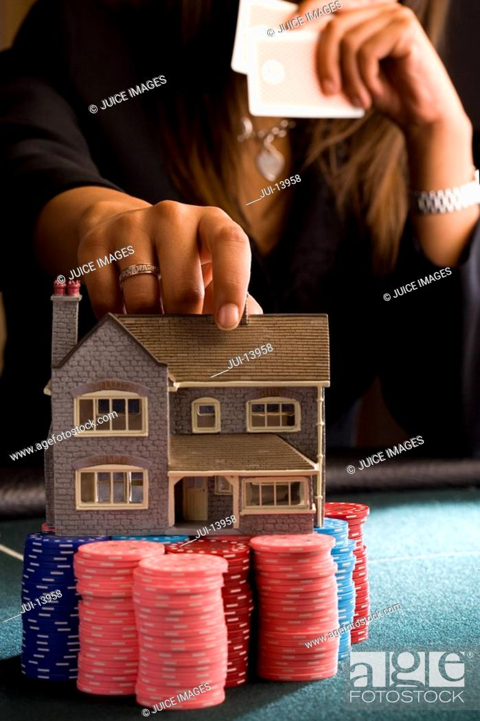 Stock Photo: Woman placing model house on pile of gambling chips on table, mid section.
