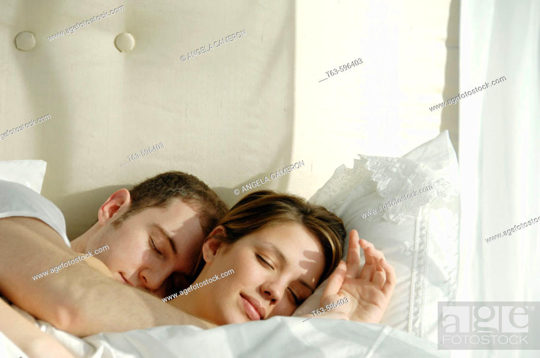 Stock Photo: Young couple sleeping and cuddling in bed together.