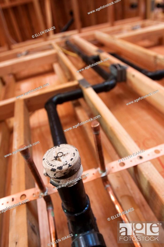 Stock Photo: Rough plumbing pipes and drain installed in a wall at residential construction site.