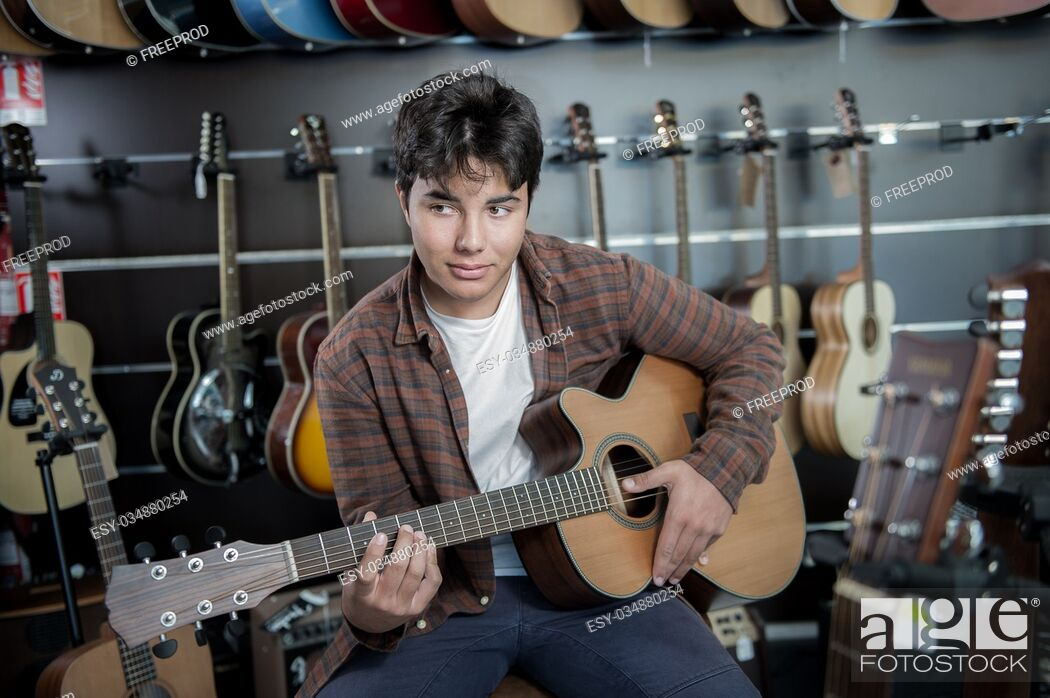 Stock Photo: Young man playing the guitar in a shop, France.