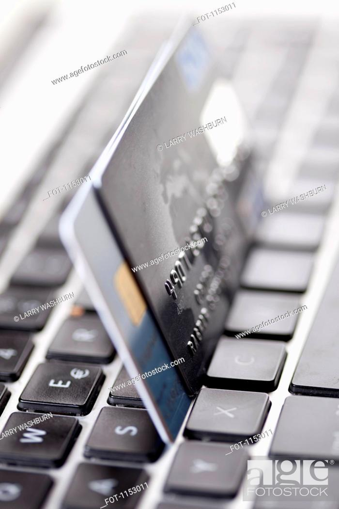 Stock Photo: Two credit cards balanced on a laptop keyboard, close-up.