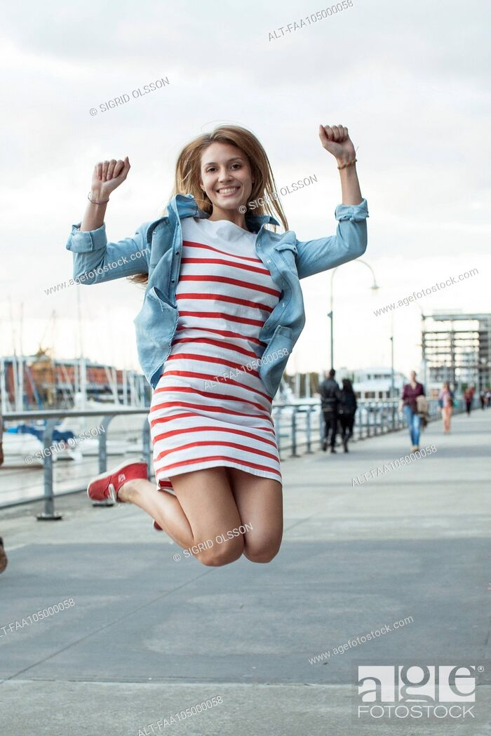 Stock Photo: Young woman jumping for joy outdoors.